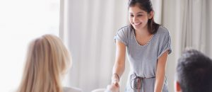 A young woman shakes the hand of an admissions advisor